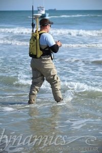 Man walking into the water for a survey