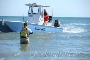 Man walking in the water with a survey boat at sea