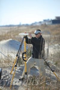 Image of man with survey equipment on the sand
