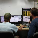 Image of two Geodynamics team members creating sidescan mosaics and seafloor bathymetry grids.