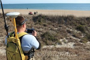 topographic surveyor on dune overlooks the beach