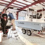 technicians work on survey boats in garage