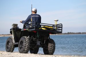surveyor on ATV with GPS antenna