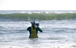surveyor wades into surf zone