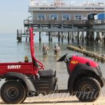 survey ATV on beach in front of pier