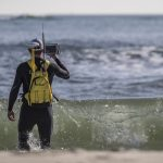 surveyor with Trimble backpack wades into surf zone